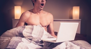 young-man-sitting-bed-and-watching-pornography-laptop